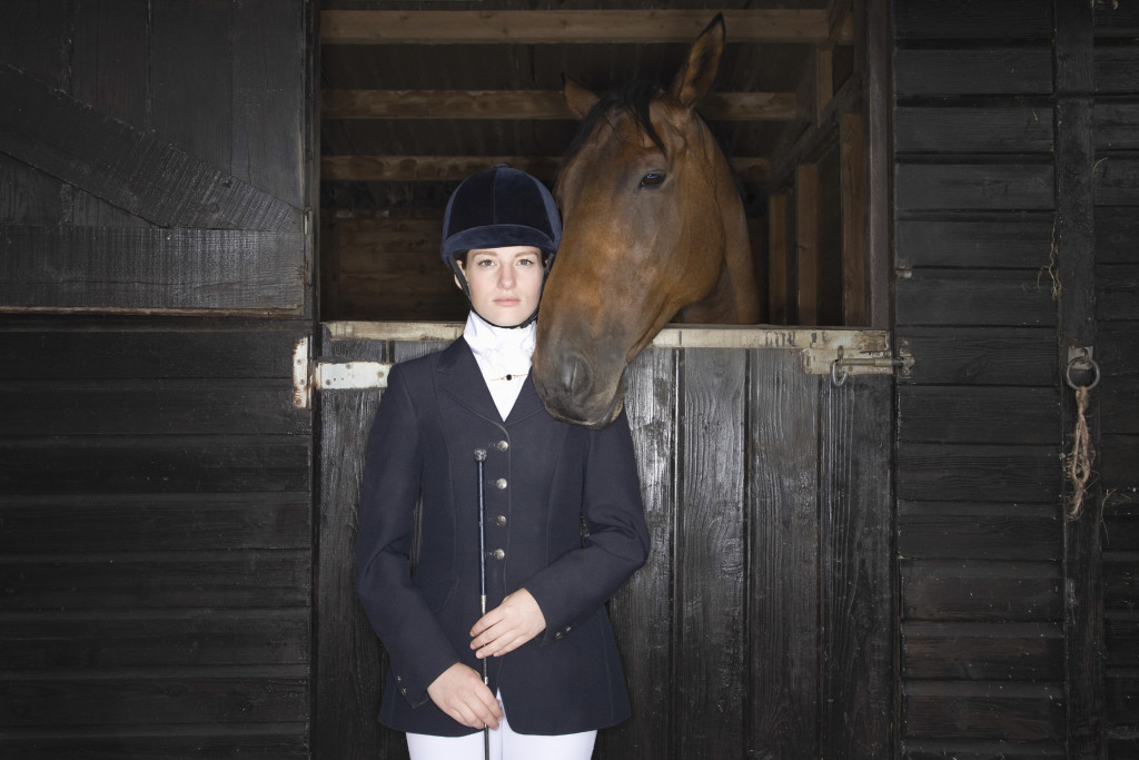 Portrait of a confident female horseback rider with horse in the stable